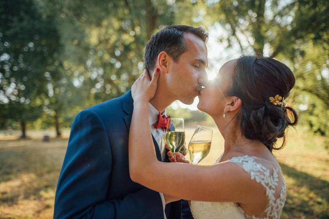 jeunes mariés s'embrasse face au coucher de soleil