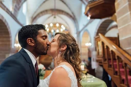 Couple de mariés s'embrasse à l'église
